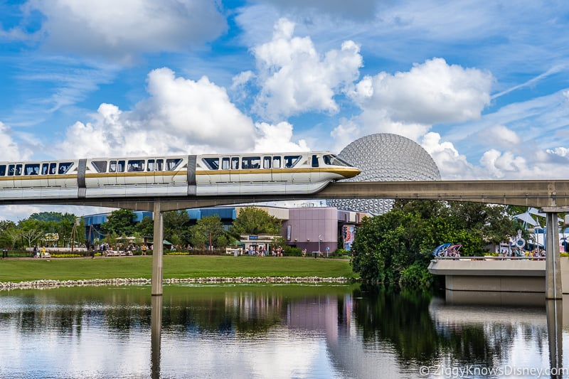Monorail passing over the water with Spaceship Earth in Epcot