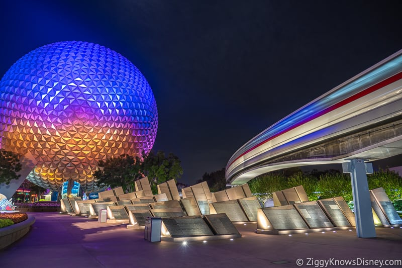 Spaceship Earth at night with the monorail passing over the Leave a Legacy Monuments