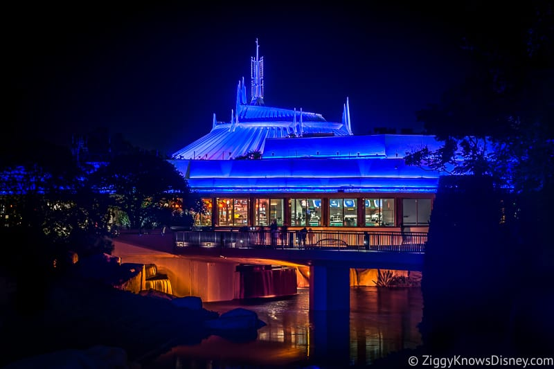 Space Mountain lit up blue at night in the Magic Kingdom