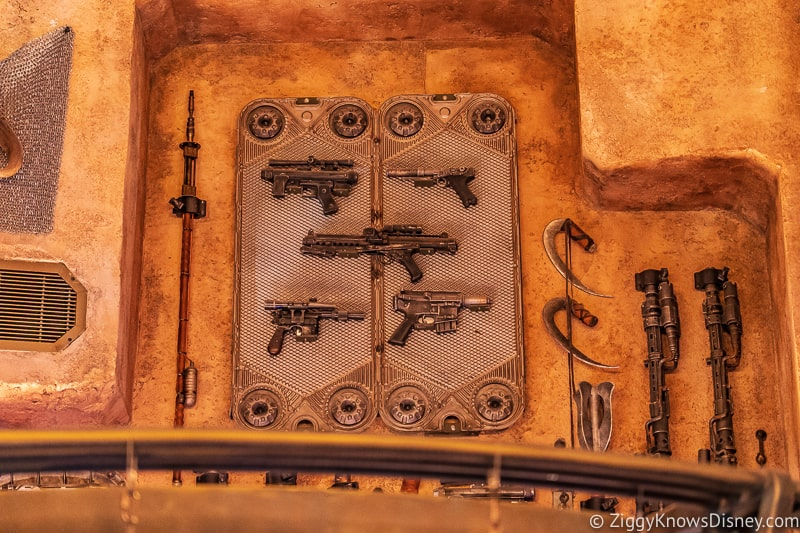blasters on the wall of Dok Ondar's Den of Antiquities Galaxy's Edge