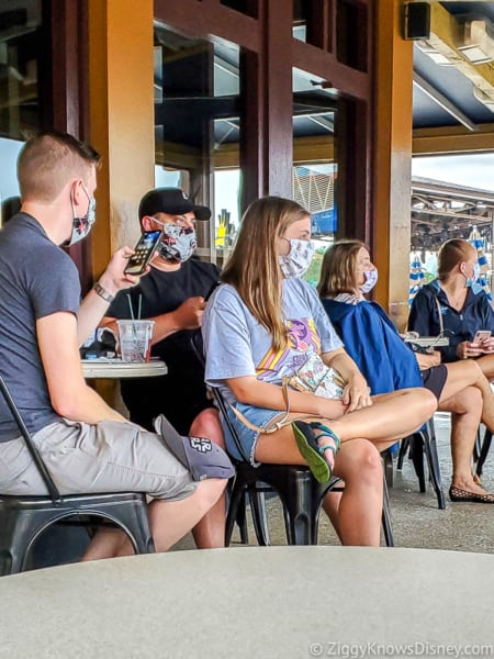 Guests sitting at tables with face masks in Disney World