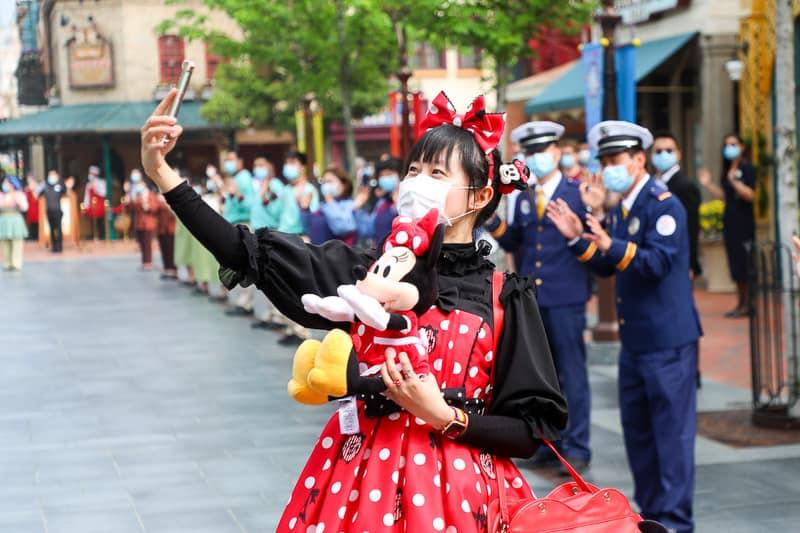 guests wearing mask taking selfie in Disney park