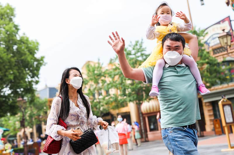 family walking through Disney Park with face masks